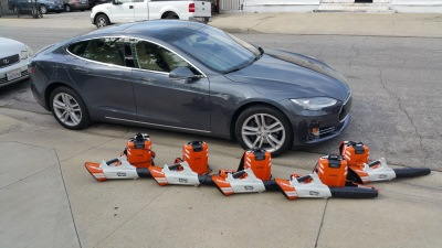 5 electric leaf blowers sitting in front of a Tesla electric car